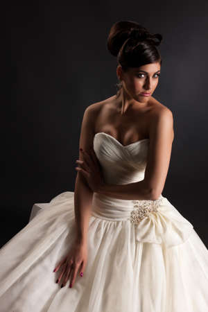 Young beautiful woman in a wedding dress on a black studio background Stok Fotoğraf
