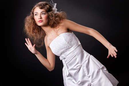 Young beautiful woman in a fashionable wedding dress on a black background