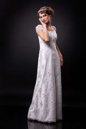 Young beautiful woman in a fashionable wedding dress on a black background Stock fotó
