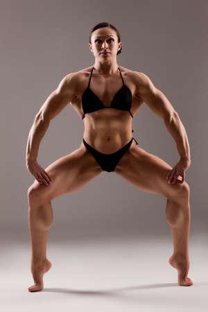Woman bodybuilder in a black swimsuit on a studio background Stock fotó