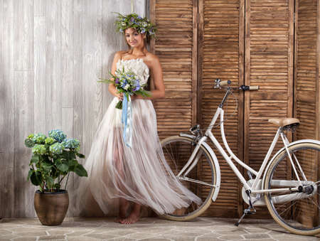 Young beautiful girl in a wedding dress with a bicycle