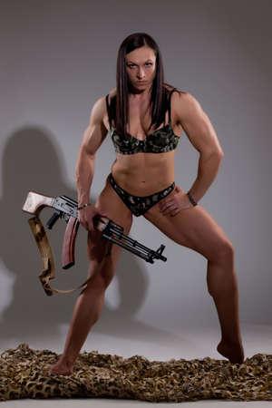 Young woman holding a machinegun