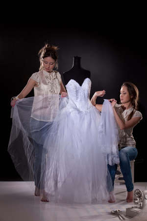 Two young twin sisters in the studio with wedding dress and tailor accessories