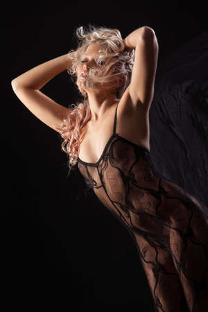 Young beautiful woman in a lingerie on a black studio background