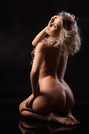 Young beautiful nude blonde woman on a black studio background Stock fotó