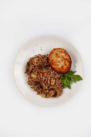 Boiled buckwheat on a plate on isolated studio background