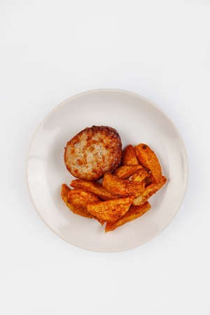 Cutlet and roasted potatoes on a plate on isolated background