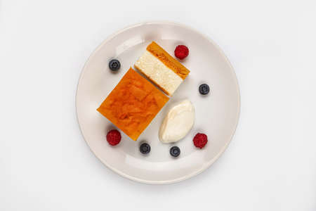 Curds with jelly and berries on a plate on isolated studio background Stock fotó