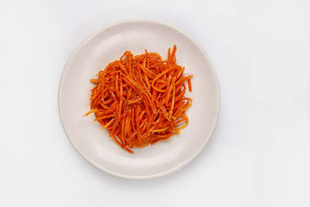 Marinaded carrots on a plate on isolated studio background