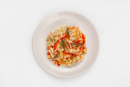 Cabbage salad with carrot on a plate on isolated studio background Stock fotó