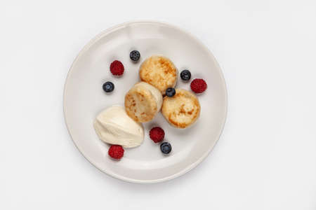 Cheese cakes and different berries on a plate on an isolated studio background