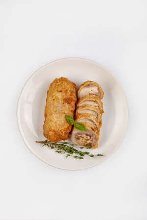 Sliced meat roll on a plate on isolated studio background