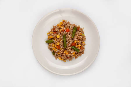 Roasted rice and vegetables on a plate on isolated background Stock fotó