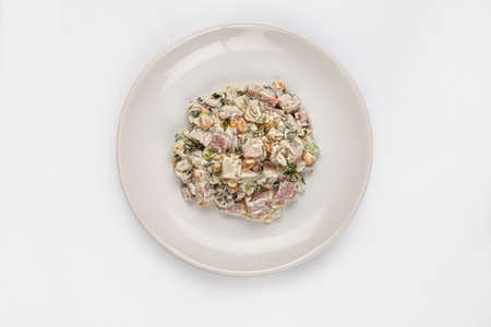 Sald with mayonnaise on a plate on isolated background