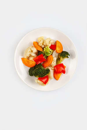 Different vegetables on a plate on an isolated studio background Stock fotó