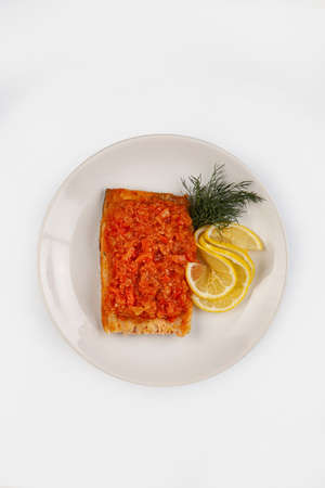 Roasted fish and lemon on a plate on an isolated studio background Stock fotó