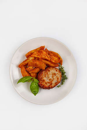 Cutlet, potatoes and greenery on a plate on isolated studio background