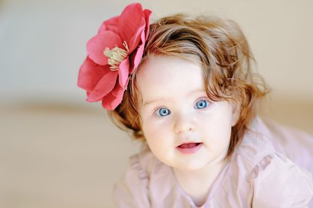 9 months: Cute 9-months baby-girl with flower on her hair smiling Stock Photo