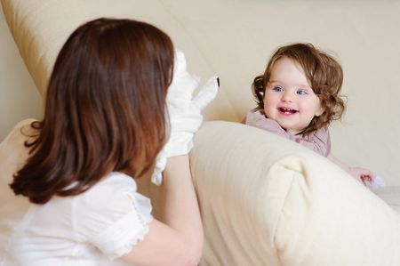 Beautiful mother plays a puppet show with a baby-daughter Stock Photo - 7790016