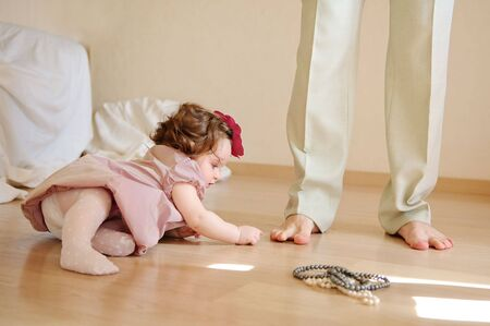 little girl feet: The girl lies on a floor and plays with feet of the daddy