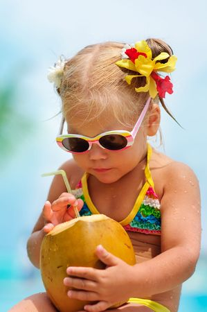 portrait of cute toddler girl with coconut cocktail in the tropical beach Stock Photo - 7874377