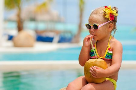 nourrisson: Portrait de tout-petits cute fille avec noix de coco cocktail dans la plage tropicale Banque d'images