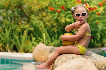 portrait of cute toddler girl with coconut cocktail in the tropical beach Stock Photo - 7951913
