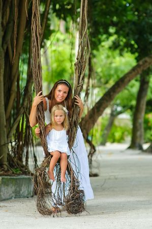 Young beautiful mother and her little cute daughter swinging on liana photo