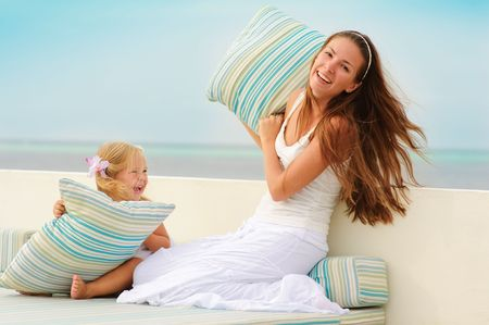 Young beautiful mother and her little cute daughter have a fun in beach cafe photo