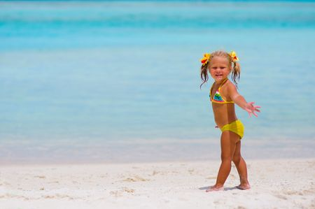 Toddler pretty girl dressed in a swimsuit standing on tropical beach photo