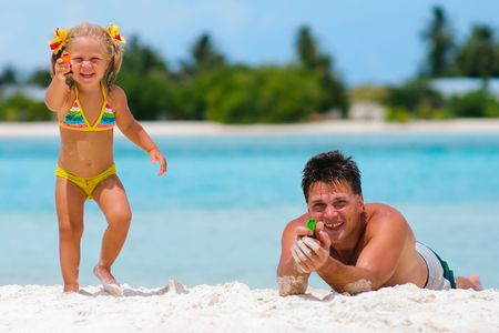 father and his cute daughter playing with water guns on exotic beach photo