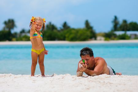 water gun: father and his cute daughter playing with water guns on exotic beach Stock Photo