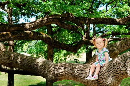 jungle girl: Cute toddler girl sitting on branch huge tree and smiling Stock Photo