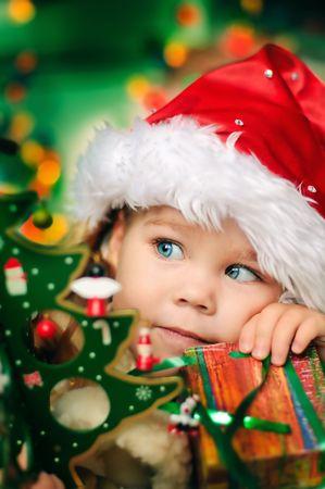 baby kerst: Gelukkig kleine meisje in Kerst muts met heden hebben een kerst feest
