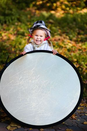 funny little girl assist the photographer with reflector photo