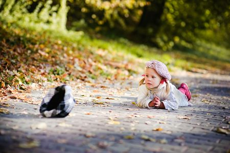 cute little girl falling down and crying in autumn park photo