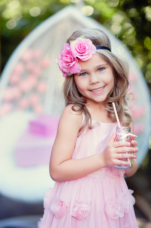 Little girl celebrate Happy Birthday Party with rose decor in\ the beautiful garden