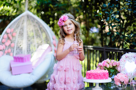 Little girl celebrate Happy Birthday Party with rose decor in the beautiful garden photo