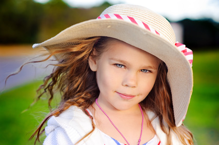 straw hat: Portrait of a fashion toddler girl in straw hat in the park