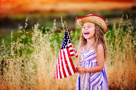 fourth july: Happy adorable little girl smiling and waving American flag outside, her dress with strip and stars, cowboy hat  Smiling child celebrating 4th july - Independence Day
