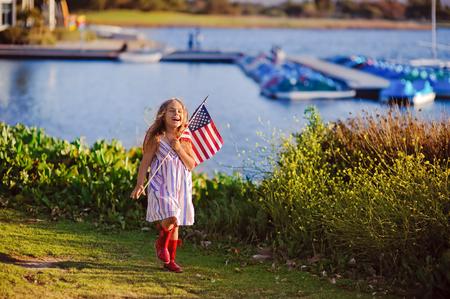 julio: Feliz adorable niña sonriendo y agitando bandera americana exterior, su vestido con la tira y las estrellas, sombrero de vaquero que celebra 04 de julio Niño sonriente - Día de la Independencia Foto de archivo