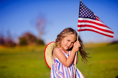 july: Happy adorable little girl smiling and waving American flag outside, her dress with strip and stars, cowboy hat  Smiling child celebrating 4th july - Independence Day