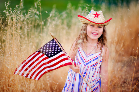 Happy adorable little girl smiling and waving American flag outside, her dress with strip and stars, cowboy hat  Smiling child celebrating 4th july - Independence Day