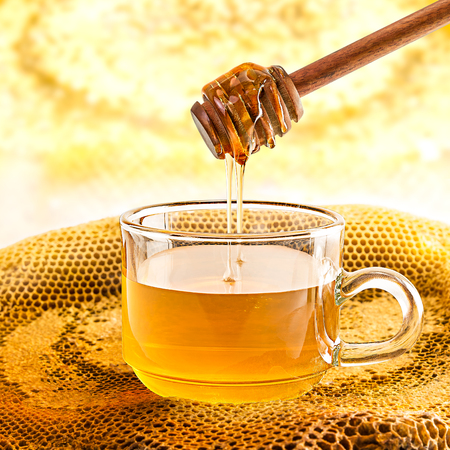 Glass of honey and honeycomb with wooden dipper Stockfoto