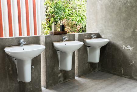 The white washbasin in public toilet photo