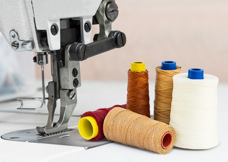 Sewing machine and bobbins of thread for textile industry