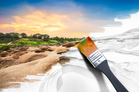 Black wooden paintbrush in the act of painting color on natural landscape image