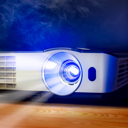 Closeup of projector for presentation on wooden table in blue light tone Stockfoto