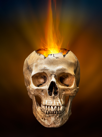 fire skull: Beam of fire blaze burst out from internal broken human skull on dark background