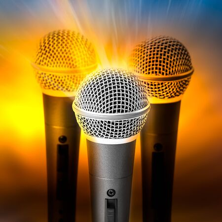 triple: Golden light on triple silver microphone on blured background